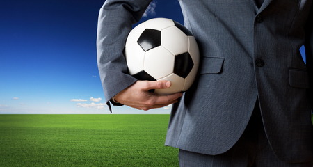 soccer ball: Businessman holding a soccer ball with blue sky and green meadow on background. Stock Photo