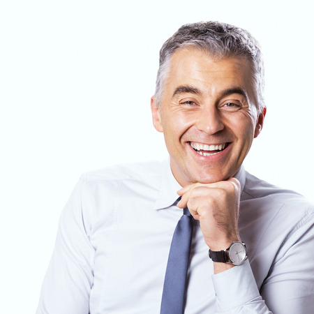 Confident businessman smiling with hand on chin and looking at camera on white background. photo