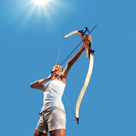buena postura: Mujer atractiva apuntando con el arco y la flecha con el cielo azul de fondo.