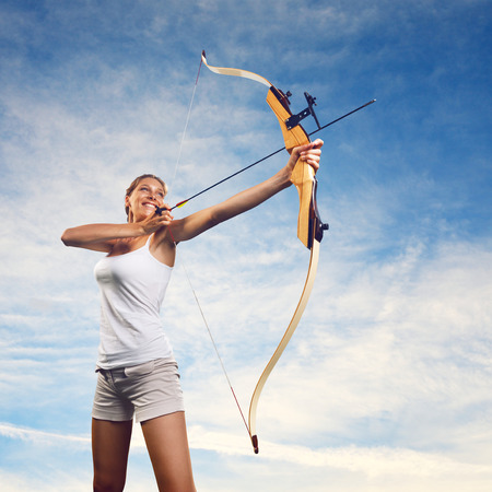 Attractive woman aiming with bow and arrow with blue sky on background. photo