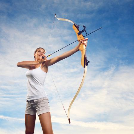 buena postura: Mujer atractiva apuntando con el arco y la flecha con el cielo azul en el fondo. Foto de archivo