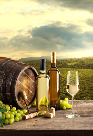 Wine bottles with barrel still life and lush natural landscape on background with vineyards. photo