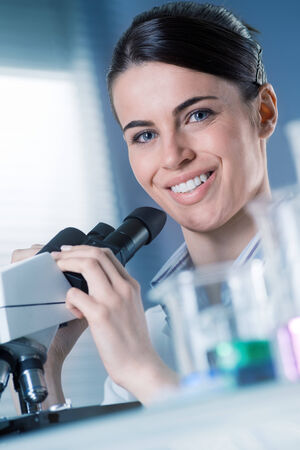 Female researcher using microscope and smiling at camera with beakers on foreground. photo