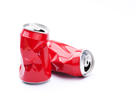 Red crushed cans on white background, recycling and pollution concept.