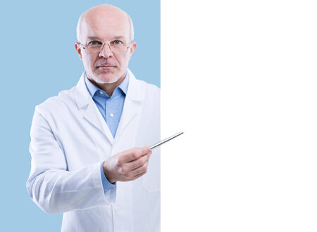 serious doctor: Senior doctor holding a big white sign and pointing with a pen, blank copyspace.