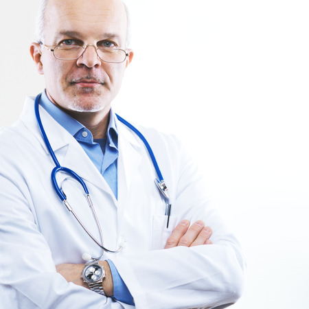 Senior confident doctor in a clinic with arms crossed.