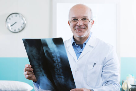 columna vertebral humana: Hombres m�dico senior mirando im�genes de rayos X de la columna vertebral humana. Foto de archivo