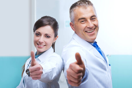 doctors smiling: Doctors with thumbs up smiling and expressing vitality.