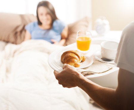 breakfast in bed: Hand holding breakfast tray to a happy relaxed woman in bed