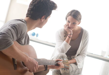 Young handsome man playing guitar for his girlfriend photo