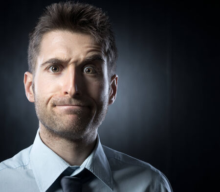 raised eyebrow: Young businessman: confused expression with raised eyebrow. Stock Photo