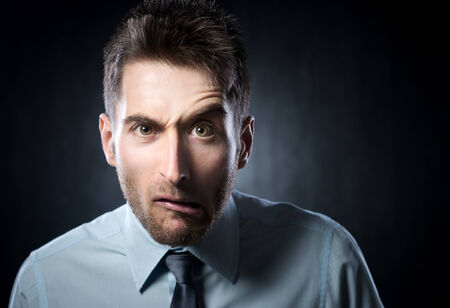 raised eyebrow: Distraught young businessman with raised eyebrow on gray background.