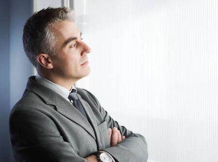 Confident businessman with arms crossed looking through a window. photo