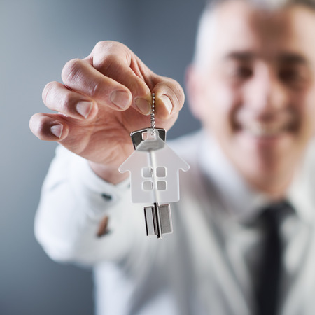 house keys: Real estate agent holding out keys of your new house.