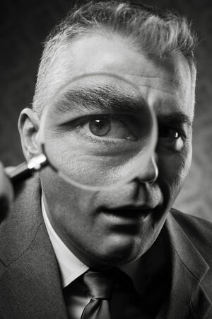 Vintage detective looking at camera through magnifying glass. photo