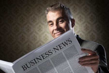 oude krant: Zakenman lezen nieuws tegen vintage behang achtergrond knappe. Stockfoto