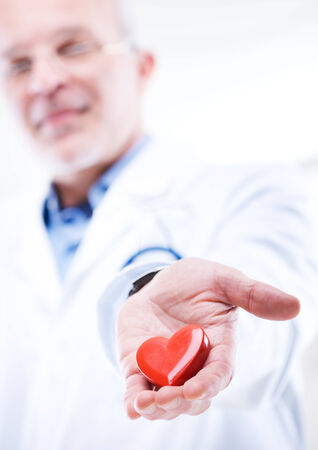 Doctor holding an heart, cardiologist and cardiovascular diseases concept. photo
