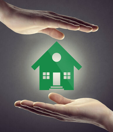 housing problems: Hands protecting green house icon on white background, home insurance and safety concept.