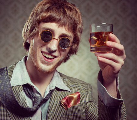 kitsch: 1960s style guy with cocaine on his nose holding a glass of whisky.