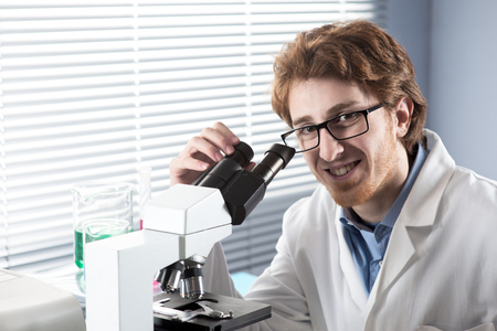 Student researcher using microscope and smiling at camera. photo