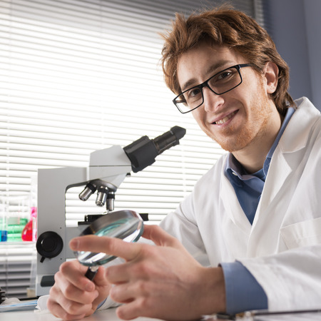 immunology: Chemical laboratory technician smiling and holding a magnifier with equipment on background.