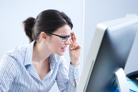 Young office worker staring at computer screen and adjusting glasses. photo