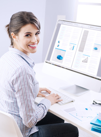 unusual angle: Young office worker smiling and typing on a  keyboard at office. Stock Photo