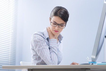 Young office worker with neck pain touching her back. photo
