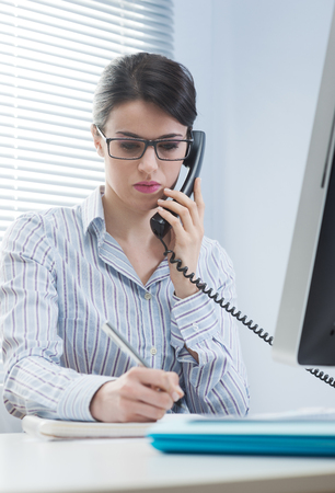 Woman working on the phone and writing down notes at office. Stock Photo - 28941862