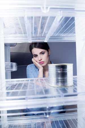 can food: Young sad woman looking at one tin in her empty fridge.