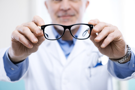 oculist: Oculist giving a pair of glasses during a visit.