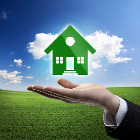 Businessman hand showing a green house icon on meadow and blue sky background. photo