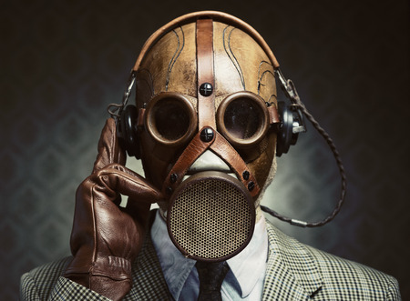 pollution: Man wearing vintage gas mask and headphones listening to music. Stock Photo