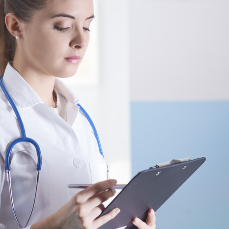 doctor writing: Young woman doctor or pharmacist in office with clipboard Stock Photo