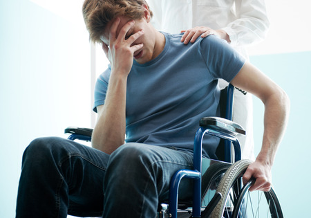 Female doctor consoling sad man sitting in wheelchair photo