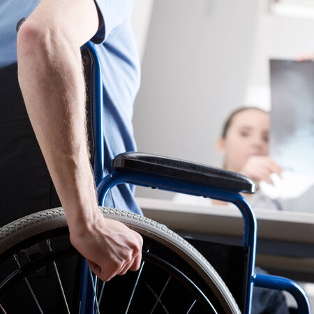 Disabled young man in wheelchair at doctors office. Doctor is looking x-ray  photo