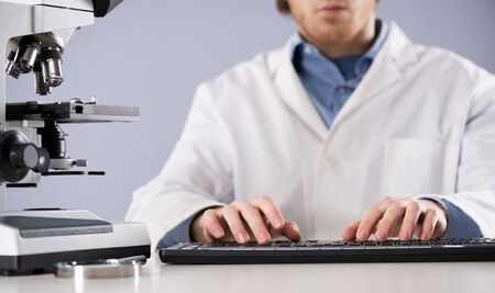 Researcher working at desk and typing on a keyboard, with microscope and magnifier. photo