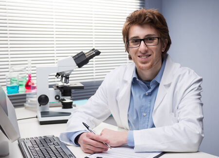 pathologist: Young researcher writing notes at desk in the chemical lab. Stock Photo