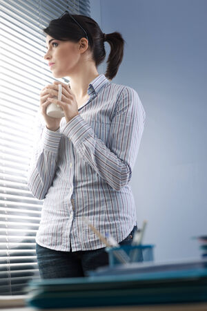 looking through window: Attractive office worker peeking out of blinds and holding a mug.