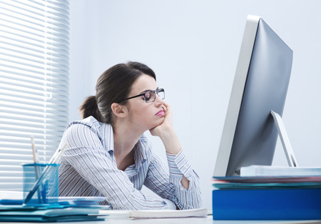 women working: Bored office worker at desk staring at computer screen with hand on chin.