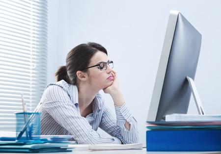 mujeres trabajando: Oficinista aburrido en el escritorio mirando la pantalla del ordenador con la mano en la barbilla. Foto de archivo