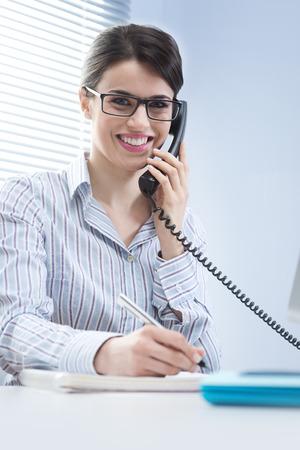 answering phone: Hermosa mujer con gafas de responder llamadas telef�nicas en el escritorio.