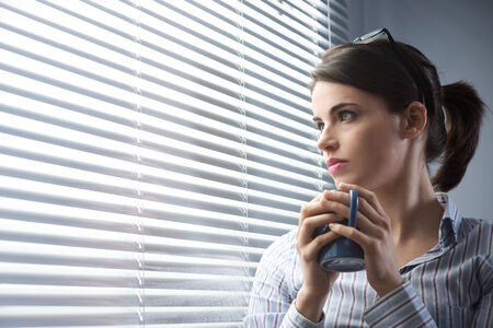 drinking problem: Pensive woman peeking through blinds and holding a cup of coffee.