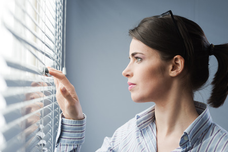 Young attractive woman peeking through blinds at window. Stock Photo
