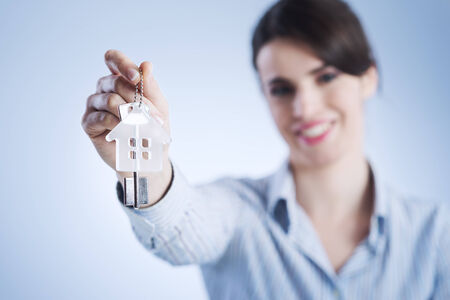 Real estate agent holding out house keys and smiling. photo