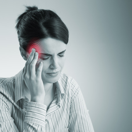 Young woman with headache touching her temples. photo