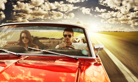 sports car: Couple taking a road trip in vintage convertible