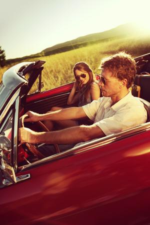Couple driving convertible car enjoying a summer day at sunset photo