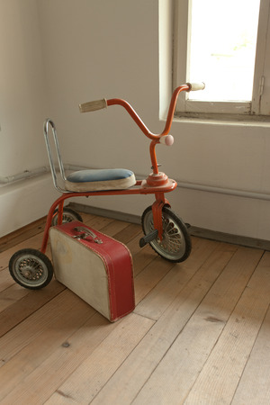 antique tricycle: Vintage red tricycle and old suitcase on hardwood floor.