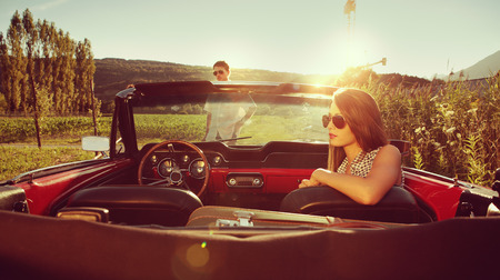 Young couple in a convertible car taking a break photo